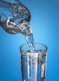 A água mineral de derramamento flui em um vidro Fotografia de Stock Royalty Free