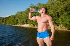 Água muscular da bebida do homem do ajuste considerável na praia Imagens de Stock