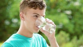 Água potável adolescente do menino fora video estoque