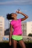 Água potável afro-americano da mulher após movimentar-se imagem de stock