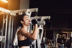 Água potável asiática da jovem mulher no gym foto de stock