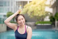 Água potável asiática nova da mulher na piscina Imagens de Stock Royalty Free