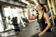 Água potável atrativa da jovem mulher do esporte foto de stock