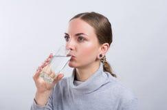 Água potável atrativa da menina no fundo claro Imagem de Stock