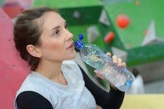 Água potável bonita da mulher da aptidão da baixa chave da garrafa Fotografia de Stock Royalty Free