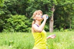 Água potável bonita da mulher da aptidão e transpiração após o exercício no dia quente do verão imagem de stock royalty free