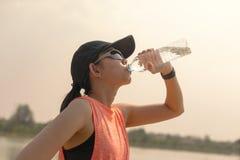A água potável bonita da mulher do atleta da aptidão após dá certo o exercício sobre ver foto de stock