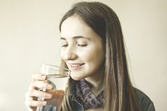 Água potável bonita feliz da jovem mulher foto de stock royalty free