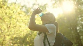 Água potável bonita nova da menina na caminhada na luz solar fotos de stock royalty free