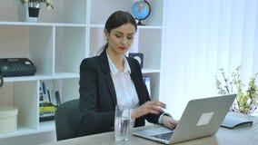 Água potável bonita nova da mulher de negócios no trabalho vídeos de arquivo