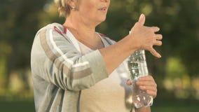 Água potável cansado da mulher da garrafa após o exercício exterior, equilíbrio do aqua filme