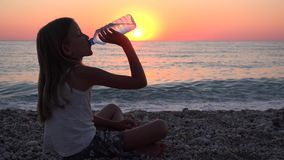 Água potável da criança na praia no por do sol, ondas de observação do mar da criança, menina no beira-mar vídeos de arquivo