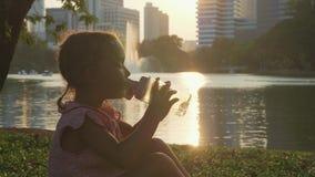 Água potável da criança no parque com lago e arranha-céus no fundo