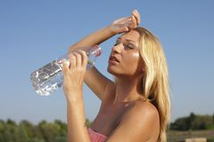 Água potável da jovem mulher no verão quente fotos de stock royalty free