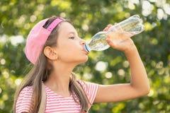 Água potável da menina da criança em um parque Fotografia de Stock Royalty Free
