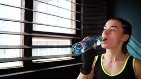 Água potável da mulher da aptidão da garrafa durante a ruptura do exercício no movimento lento do close up do gym filme