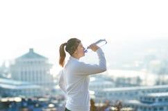 Água potável da mulher durante um corredor Tempo frio Mulher movimentando-se em uma cidade durante um inverno Dia ensolarado Modo Fotos de Stock Royalty Free