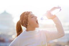 Água potável da mulher durante um corredor Tempo frio Mulher movimentando-se em uma cidade durante um inverno Dia ensolarado Modo Imagens de Stock Royalty Free