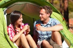 Água potável de acampamento dos pares na barraca feliz Fotografia de Stock Royalty Free