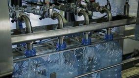 Água potável de engarrafamento em umas garrafas plásticas na empresa da oficina dentro vídeos de arquivo
