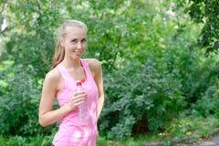 Água potável desportiva da jovem mulher da garrafa Fazendo o esporte exterior fotos de stock