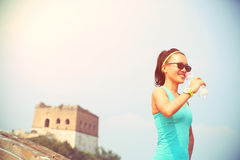 Água potável do atleta do corredor da mulher no Grande Muralha chinês Imagens de Stock