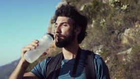 Água potável do caminhante ao estar na montanha contra o céu vídeos de arquivo