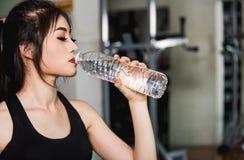 Água potável do esporte do estilo de vida da menina da jovem mulher na garrafa após o exercício do exercício cardio- foto de stock royalty free