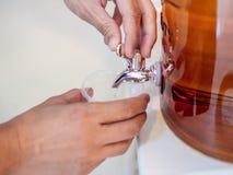 Água potável do fillilg das mãos do close-up no copo plástico do refrigerador de vidro foto de stock