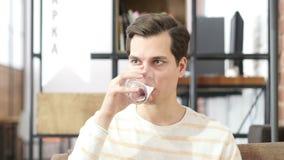 Água potável do homem novo que senta-se em um sofá em casa e que olha a câmera vídeos de arquivo
