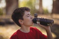 Água potável do menino após o exercício durante o curso de obstáculo imagem de stock royalty free