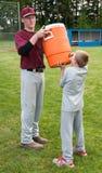 Água potável do menino após um jogo de basebol fotos de stock royalty free