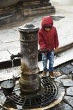 água potável do menino da torneira fora Imagem de Stock