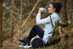 Água potável do trekker da mulher na floresta foto de stock