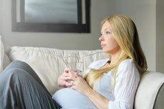 Água potável emocional da mulher gravida e olhar a janela da saída calmamente imagem de stock royalty free