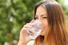 Água potável feliz da mulher de um vidro exterior