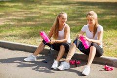 Água potável feliz das moças após um exercício em um fundo natural Conceito saudável do estilo de vida Fotografia de Stock Royalty Free