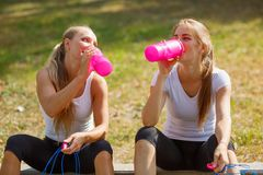 Água potável feliz das moças após um exercício em um fundo natural Conceito saudável do estilo de vida Imagem de Stock Royalty Free