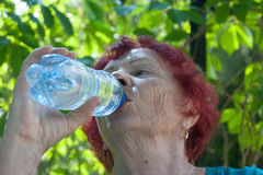 Água potável idosa da mulher da garrafa Imagem de Stock Royalty Free