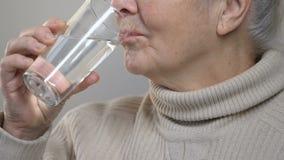 Água potável idosa enrugada da mulher, sentindo sedento, tomando a medicina, close up filme