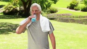 Água potável madura feliz do homem ao estar ereto filme