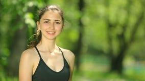 Água potável magro da jovem mulher após a formação O atleta da mulher toma uma ruptura, ela água potável, para fora em uma corrid filme