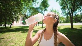 Água potável magro da jovem mulher após a formação O atleta da mulher toma uma ruptura, ela água potável, para fora em uma corrid vídeos de arquivo