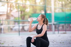 Água potável nova asiática da mulher da aptidão após movimentar-se foto de stock