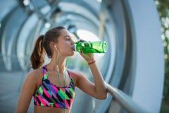Água potável saudável da jovem mulher e escuta a música após o exercício Imagens de Stock Royalty Free