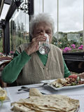 Água potável superior da mulher ao ter o almoço em um restaurante imagem de stock royalty free