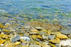 Água pouco profunda com pedras para dentro Fotografia de Stock Royalty Free