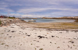 Água pouco profunda na baía, Sandy Beach, um cais no fiorde, barco amarrado Foto de Stock Royalty Free