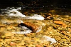 Água que apressa-se sobre Boulder no córrego pequeno imagem de stock royalty free