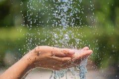 Água que derrama nas mãos do ` s da mulher fotografia de stock
